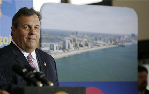 New Jersey Gov. Chris Christie smiles as he stands near a photograph of Atlantic City in Newark Liberty International Airport in Newark, N.J., Thursday, Nov. 14, 2013, during an announcement that  ...