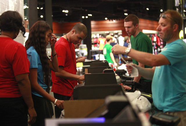 Sales associates, left, assist customers at the registers at the new Nike store at the Forum Shops at Caesars Palace in Las Vegas on the opening day, July 28, 2011. (File, JESSICA EBELHAR/LAS VEGA ...