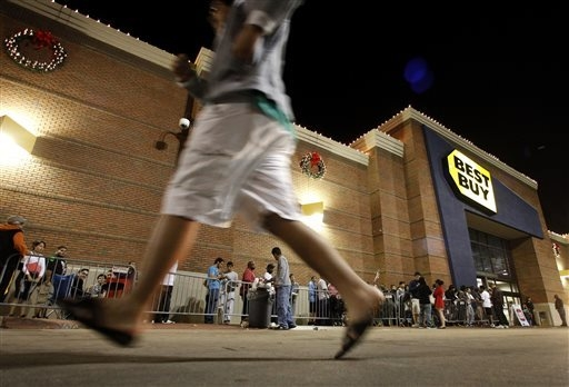 In this Thursday, Nov. 22, 2012, file photo, shoppers stand in line outside a Best Buy department store before the store's opening at midnight. Thanksgiving is slowly becoming just another shoppin ...