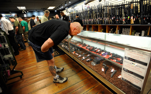 Mark Kruger of Las Vegas looks at a display case of hand guns at Discount Firearms and Ammo on Saturday, Oct. 26, 2013. (David Becker/Las Vegas Review-Journal)
