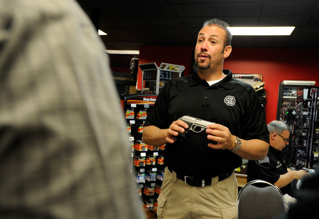Chris Hoel, national account manager at Sig Sauer gives a demonstration to customers at Discount Firearms and Ammo on Saturday, Oct. 26, 2013. (David Becker/Las Vegas Review-Journal)