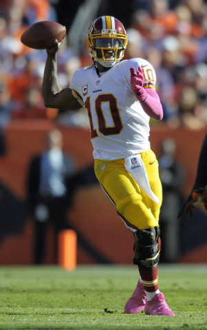 Washington Redskins quarterback Robert Griffin III looks to throw against the Denver Broncos  during an NFL football game Sunday, Oct. 27, 2013, in Denver. (AP Photo/Jack Dempsey)