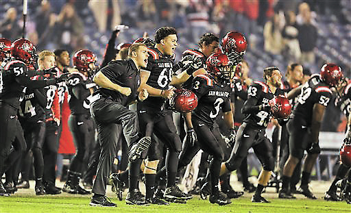 The San Diego State races on the field celebrating their 34-31 overtime victory against Boise State in an NCAA college football game Saturday, Nov. 23, 2013, in San Diego. (AP Photo/Lenny Ignelzi)