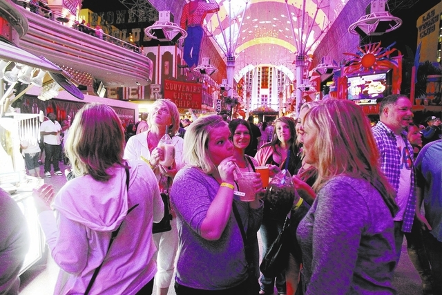 Revelers, who declined to give their names, drink at the Fremont Street Experience Friday, Oct. 4, 2013. More than 1,300 open container violations have been tossed from the Municipal Court system  ...