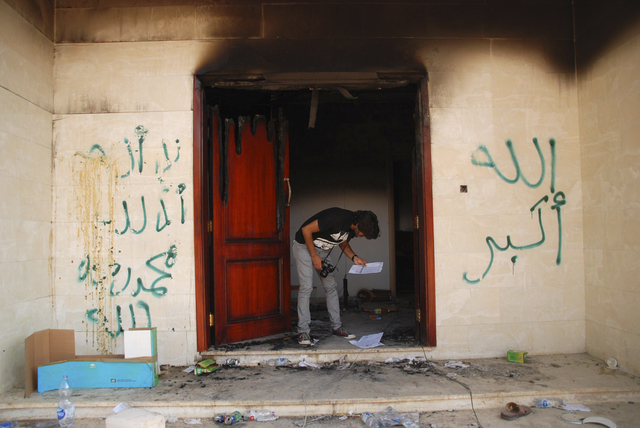 A man looks at documents at the U.S. consulate in Benghazi, Libya, after an attack on Sept. 12, 2012, that killed four Americans, including Ambassador Chris Stevens. (AP Photo/Ibrahim Alaguri, File)