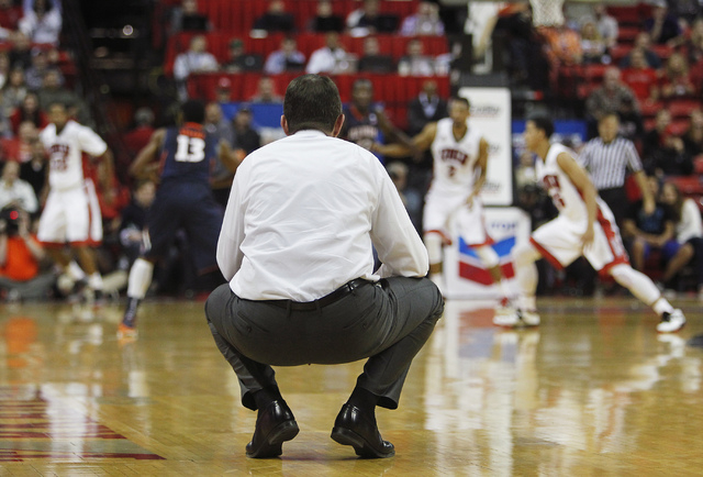UNLV head coach Dave Rice watches the action from a curious position on the floor while taking on Illinois at the Thomas & Mack Center in Las Vegas on Nov. 26, 2013. (Jason Bean /Las Vegas Review- ...
