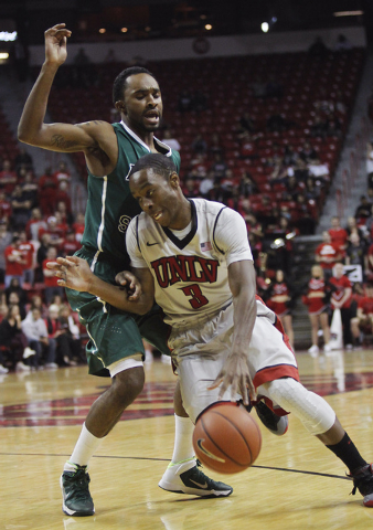UNLV's Kevin Olekaibe (3) drives past Adams State's Kenny Morgan (0) during their exhibition basketball game at the Thomas & Mack Center in Las Vegas on Nov. 5, 2013. (Jason Bean/Las Vegas Review- ...