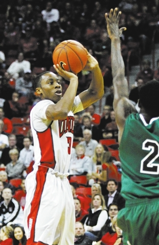 UNLV's Kevin Olekaibe (3) shoots a three pointer while being guarded by Adams State's Chuck Cole (2) during their exhibition basketball game at the Thomas & Mack Center in Las Vegas on Nov. 5, 201 ...
