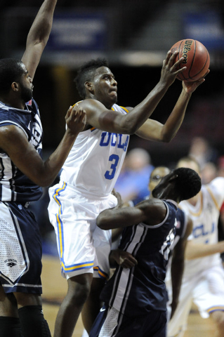UCLA Bruins guard Jordan Adams is fouled by Nevada Wolf Pack forward Cole Huff, right, while center Ronnie Stevens, left, also defends in the first half of their NCAA Basketball game in the Las Ve ...