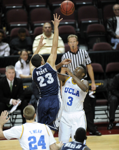 UCLA Bruins guard Jordan Adams, 3, battles Nevada Wolf Pack guard Michael Perez, 24, for a loose ball in the first half of their NCAA Basketball game in the Las Vegas Invitational college basketba ...