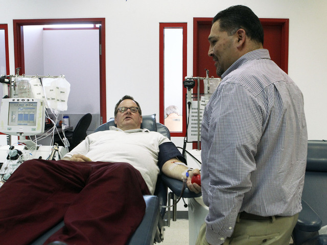 Jon Pope, left, talks with Danny Cervantes, regional donor recruitment director, at United Blood Services in Las Vegas, Monday, Nov. 11, 2013. Pope donates platelets, which are used in cancer trea ...