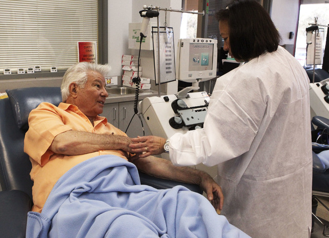 Gene Mitchell talks with Victoria Jarina, a phlebotomist at United Blood Services in Las Vegas, Monday, Nov. 11, 2013. Mitchell is donating platelets, which are used in the treatment of cancer. (J ...