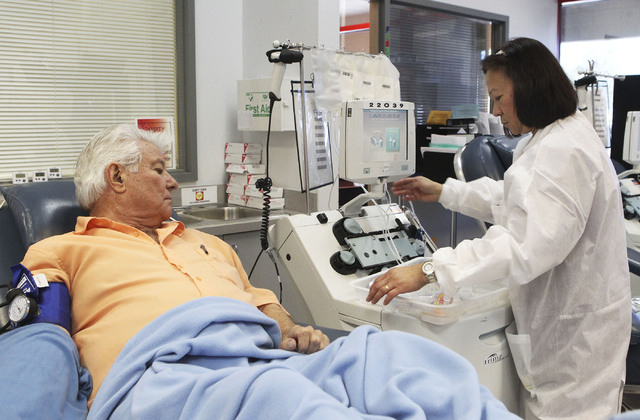 Gene Mitchell watches as Victoria Jarina, a phlebotomist, sets up the machine to collect platelets at United Blood Services in Las Vegas, Monday, Nov. 11, 2013. Platelets are used in the treatment ...