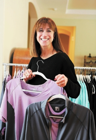 Susan Merritt, president of Live Life Large, holds several garments from her clothing line in her home Friday, Nov. 8, 2013, in Las Vegas. Merritt's line features plus-size active wear for women ...