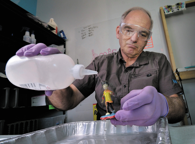 Mike Emminger, a partner at MakeIt, a 3-D printing company, covers a figurine with Super Glue to strengthen the powder-based object at the firm's offices at 5075 W. Diablo Drive in Las Vegas on We ...