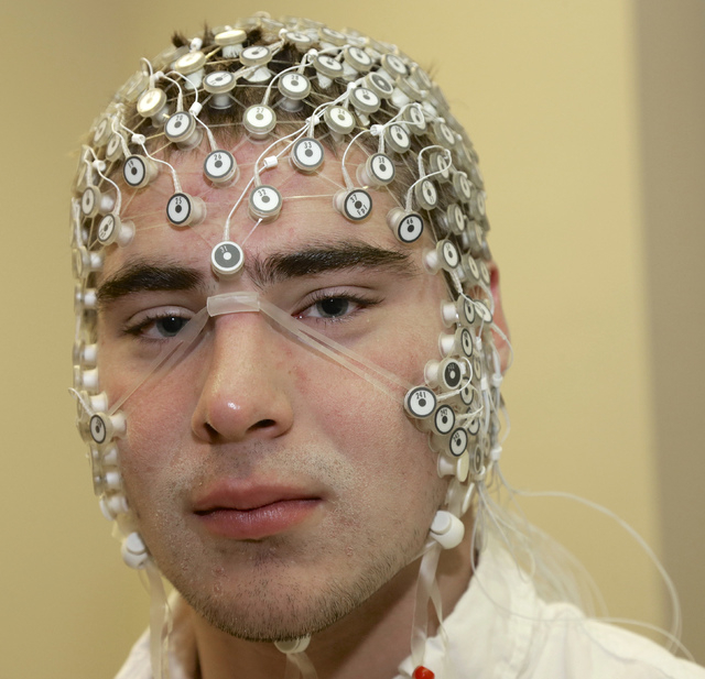 In this May 31, 2013, photo, research assistant Kevin Real wears an EEG net for detecting brain activity, at the University of Nebraska's Center for Brain, Biology and Behavior in Lincoln, Neb. Th ...