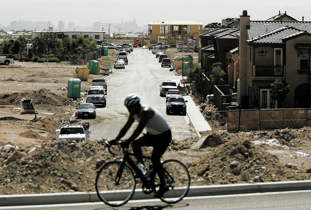 A cyclist rides by a new neighborhood taking shape in far west Las Vegas in the Summerlin development, Tuesday, Aug. 23, 2005. Sales of new homes shot up to a record high in July, the Commerce Dep ...