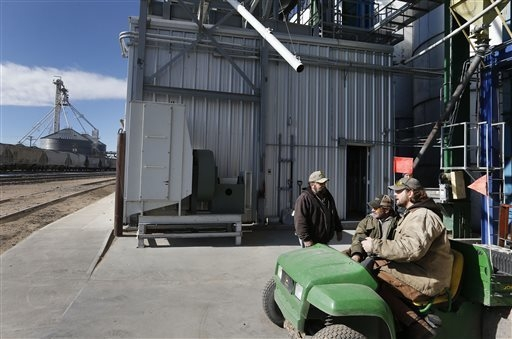 In this Nov. 6, 2013 photo, workers, left to right, Dan Dannar, Jeff Brown, and Kevin Orr talk at Global Harvest Foods, which produces birdseed and other grains, in the rural town of Akron, the co ...