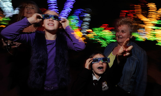 Visitors Sienna Tobler, 10, left, and Katie Kriey, 7 use 3D glasses to admire the lights as Mary Ann O'Reilly looks on during the 20th annual Holiday Cactus Lighting at Ethel M Chocolates Cactus G ...