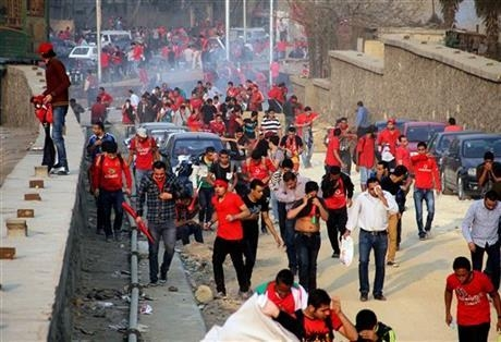 Supporters of Egyptian club Al Ahly run from tear gas during clashes with police outside a stadium ahead of the African Champions League final in Cairo, Egypt, Sunday, Nov. 10, 2013. Police used t ...