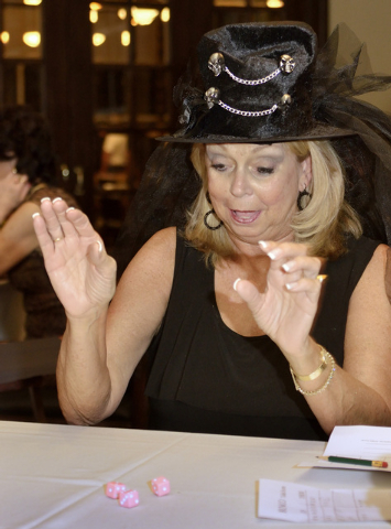 Nancy Fullerton rolls the dice during a Halloween-themed Ladies Bunco Night at the Canyon Gate Country Club at 2001 Canyon Gate Drive in Las Vegas on Thursday, Oct. 24, 2013. The group meets for t ...