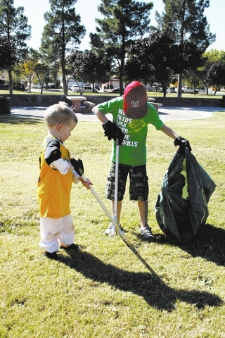 Tyler Miracle, 3, and Casey McCabe, 7, pick up trash with their parents and other volunteers Oct. 19 at West Flamingo Park as part of a community service project organized by the Commercial Allian ...