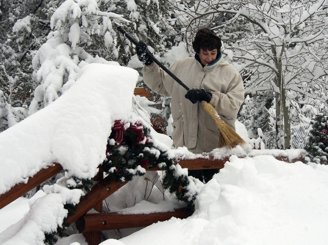 Liz Claggett clears snow off her fence in Kyle Canyon's Old Town on Mt. Charleston, Friday, Nov. 22, 2013. (Jerry Henkel/Las Vegas Review-Journal)