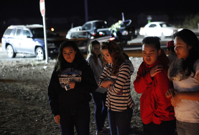 People look at a memorial for 14-year-old Helen Liu, who was killed last weekend, as floodlights illuminate a three-car crash behind them at the corner of Blue Diamond Road and Cimarron Road in La ...