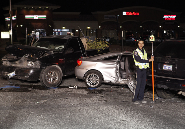 Nevada Highway Patrol officers investigate a crash at the corner of Blue Diamond Road and Cimarron Road in Las Vegas Thursday. The crash happened during a vigil for 14-year-old Helen Liu who was k ...