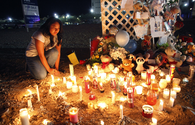 13-year-old Irene Beltran kneels by a memorial at the corner of Blue Diamond Road and Cimarron Road in Las Vegas Thursday, Nov. 14, 2013. The memorial is for 14-year-old Helen Liu who was killed w ...