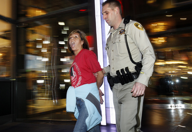 Las Vegas police arrest and remove from the casino a Culinary Union member who had protested inside of the Cosmopolitan hotel and casino in Las Vegas Friday, Nov. 1, 2013. (John Locher/Las Vegas R ...