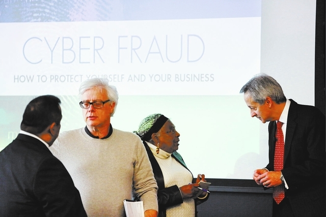 Jabie Abercrombie, center right, speaks to Jeff Lanza, far right, at Thursday's a Cyber Fraud talk. Lanza said businesspeople need to be particularly vigilant about protecting their infomration  ...