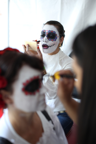 El Tiempo's Maria Matta, rear, puts on her makeup while preparing to open her publication's booth at the Day of the Dead celebration at Springs Preserve on Friday, Nov. 1, 2013. Cindy Slanec, left ...