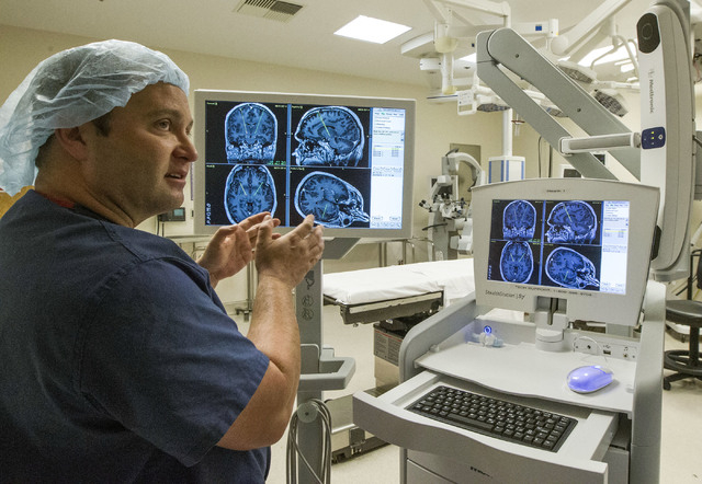 Neurosurgeon James Forage explains an MRI of Kip Smith's brain at Sunrise Hosptial in Las Vegas, Monday, Nov. 18, 2013. Smith is a Parkinson's Disease patient who received a deep brain stimulator. ...