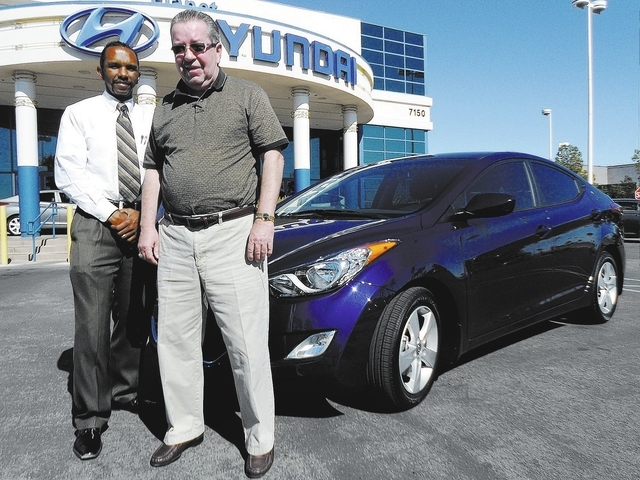Las Vegas resident Bill Bennett, right, is shown with Planet Hyundai Sahara sales consultant Tony Fisher, who has sold him three Hyundais in the past two years. including a 2013 Hyundai Elantra. C ...