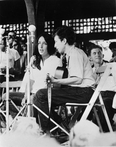 Folk singers Joan Baez, left, and Bob Dylan perform at the Newport Jazz Festival in Newport, R.I. in 1963. Two years later at the Newport Folk Festival, Dylan would pick up an electric guitar -- n ...