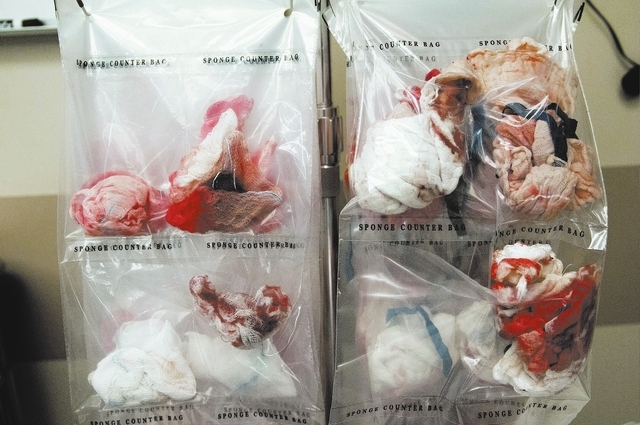 Counter bags are seen holding bloody sponges used during a breast reconstruction surgery inside the operation room at UMC, Friday, Oct. 25, 2013, in Las Vegas. Environmental service aides act as t ...