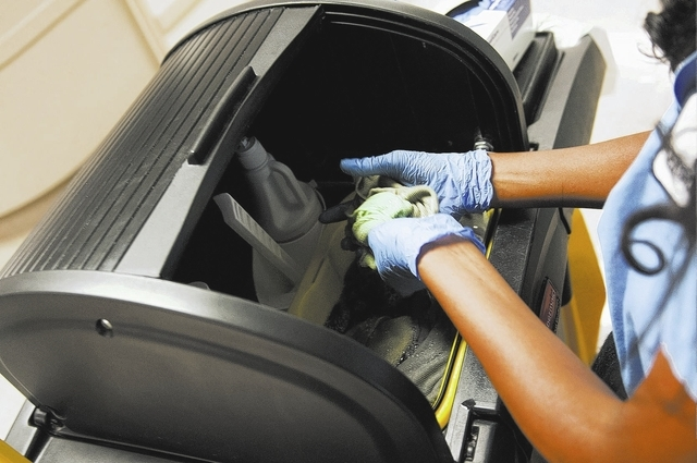 Seble Balcha, an environmental service aide at UMC, is seen rinsing one of the rags she was using to clean a room of a discharged patient, Friday, Oct. 25, 2013, in Las Vegas. Environmental servic ...