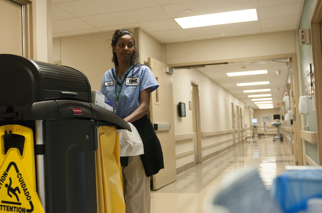 Seble Balcha, an environmental service aide at UMC, is seen pushing a cart with cleaning supplies in one of the halls, Friday, Oct. 25, 2013, in Las Vegas. Environmental service aides act as the f ...