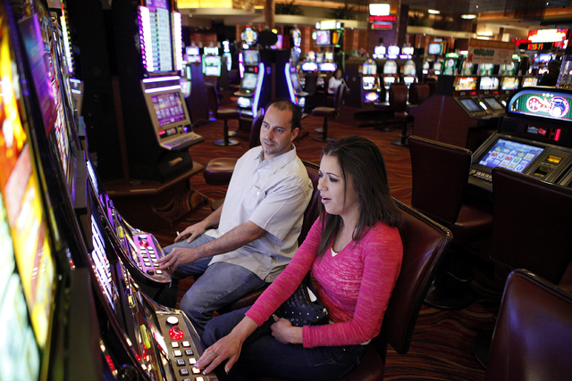 Ty Pierce, left, and Jamie Castle play slots at the Red Rock Resort in Las Vegas Thursday, Oct. 31, 2013. (John Locher/Las Vegas Review-Journal)