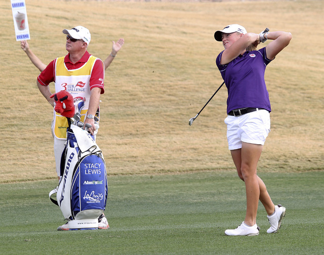 "Stacy Lewis and her caddy watch her drive on the 11th fairway during the Wendy's 3-Tour Challenge at the Rio Secco Golf Club in Henderson, Tuesday, Nov. 12, 2013.  A course worker with a ""qui ..."