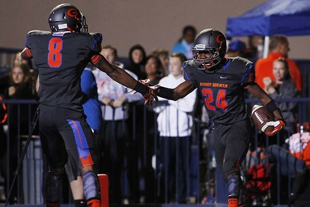 Bishop Gorman Gaels football player Russell Booze (24) gets congratulated by teammate Alize Jones (8) after scoring a first half touchdown against the Booker T. Washington Tornados Las Vegas in Oc ...