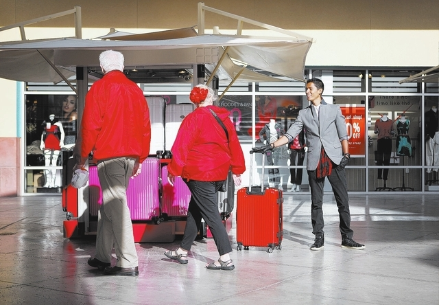 Hector Jimenez, right, sells luggage from the Easy Going kiosk at the Premium Outlet Malls North in Las Vegas Thursday, Nov. 28, 2013. (John Locher/Las Vegas Review-Journal)