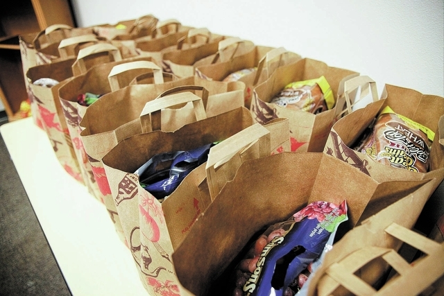 Bags prepared with one week's worth of groceries are set out for attendees of a 10-week course on budget management and food choices at HopeLink, 178 Westminster Way in Henderson Monday, Nov. 11,  ...