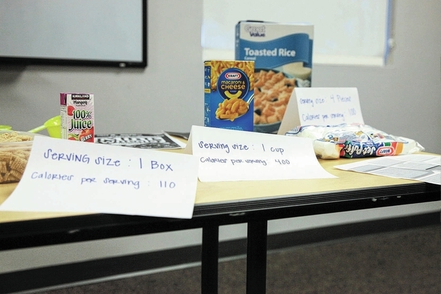 A display demonstrates expected serving sizes and calorie counts of a variety of foods at a 10-week course on budget management and food choices at HopeLink at 178 Westminster Way in Henderson Mon ...