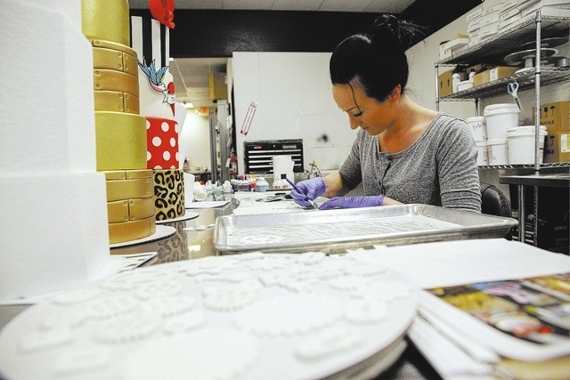 Co-owner Kristen LoVullo carves out pieces as part of a themed cake at Gimme Some Sugar Bake Shoppe 19 S. Stephanie St. Henderson, Tuesday, Nov. 19, 2013. The shop, due to open Nov. 29, 2013, is e ...