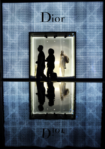 A couple is reflected in a fountain as they walk by a shop at Crystals at City Center in Las Vegas Thursday, Dec. 13, 2012. (John Locher/Las Vegas Review-Journal)