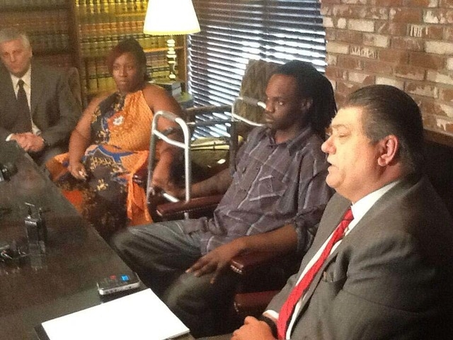 Antoine Hodges sits next to his lawyer, Cal Potter, at a news conference on Friday, Nov. 2, 2013. Hodges was shot by a Las Vegas Metropolitan Police Department officer at a 7-Eleven store in Octob ...