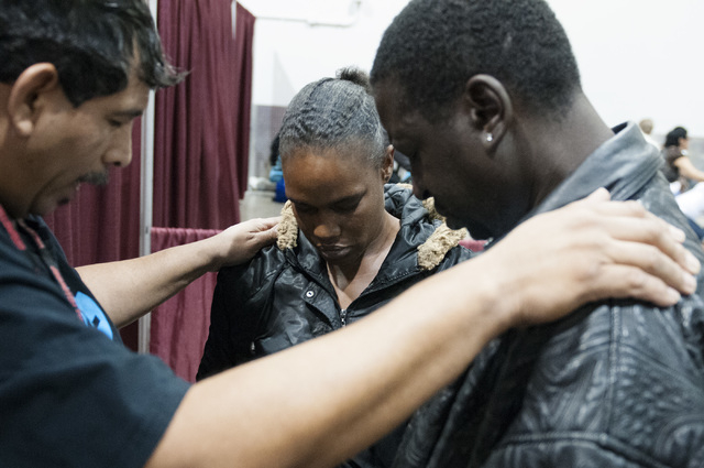 Jesus Martinez, volunteer at Valley Bible Fellowship, says a prayer with Lakeesha Allums and her fianc Marlund Martin, from left, during the annual Homeless Connect event at Cashman Center in Las  ...