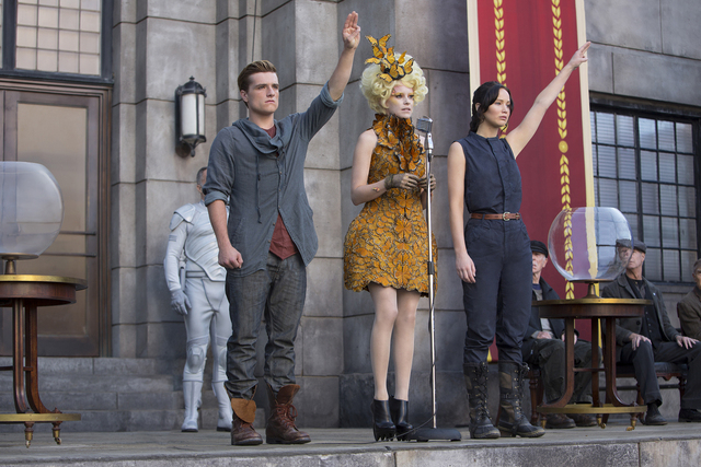 "Katniss Everdeen (Jennifer Lawrence, right), Effie Trinket (Elizabeth Banks, center) and Peeta Mellark (Josh Hutcherson, left) in ""The Hunger Games: Catching Fire."" (MURRAY CLOSE/LIONSGATE)"